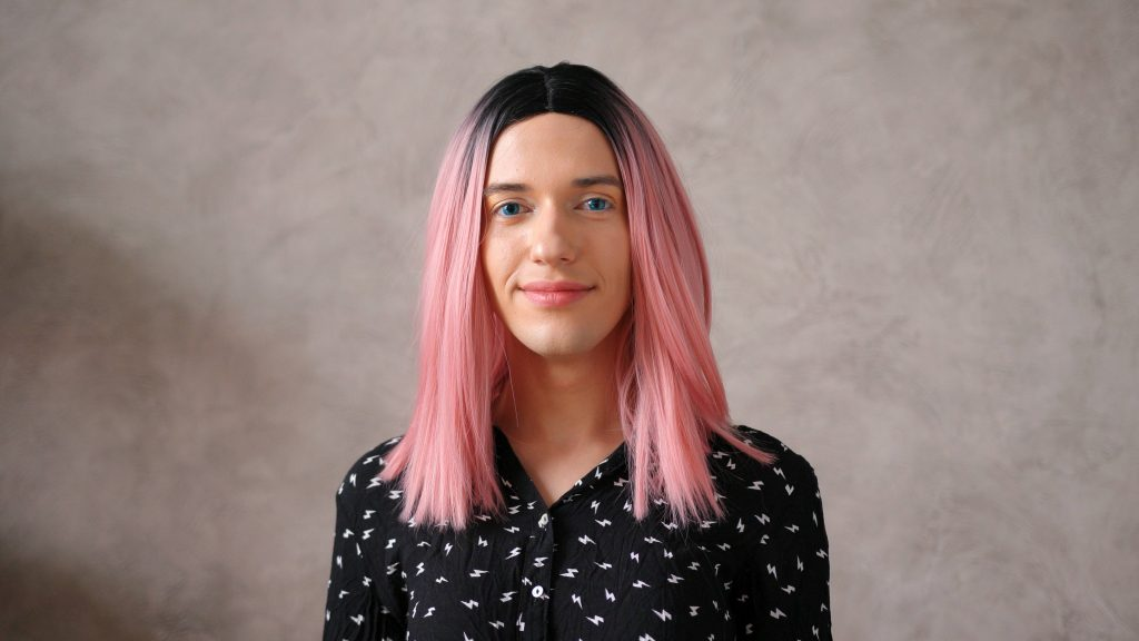 Transwoman smiling in black dot dress with pink wig poses in front of beige wall