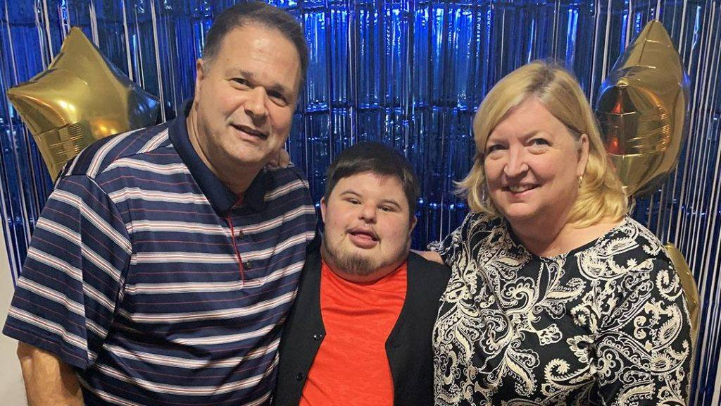 patient Tyler White, who has Down syndrome, with his mom and dad standing on each side, balloons in background, everyone smiling
