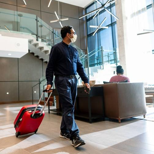 a man, perhaps Latino, wearing a mask walking through a hotel lobby with a traveling suitcase