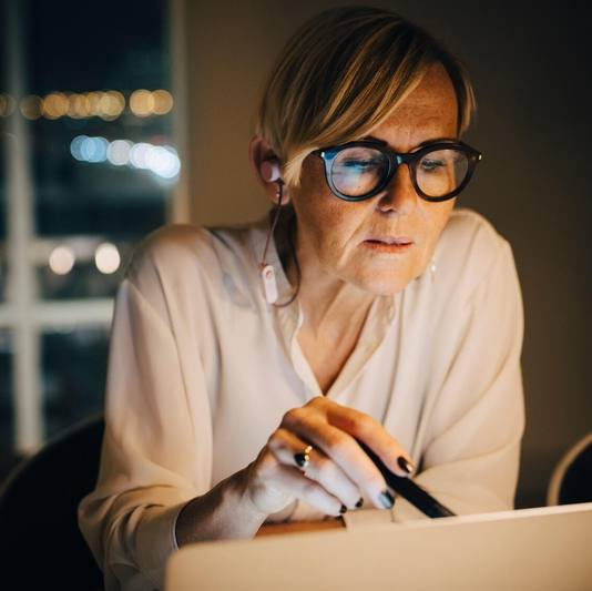 a white middle aged woman wearing eye glasses, working on a laptop computer at night