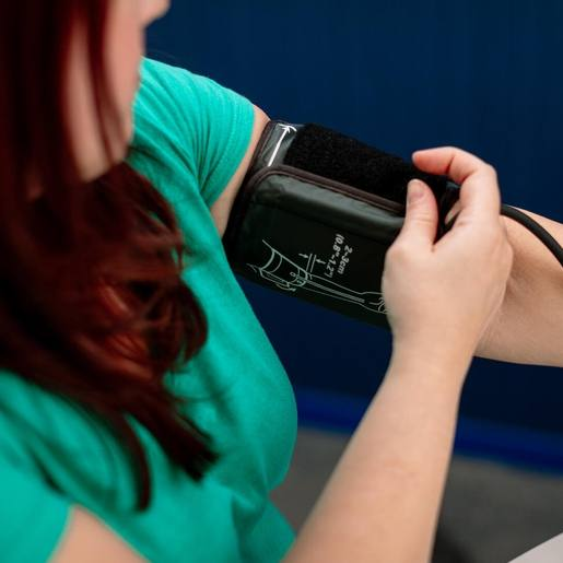 a white woman in a green shirt wrapping a blood pressure cuff around her left arm