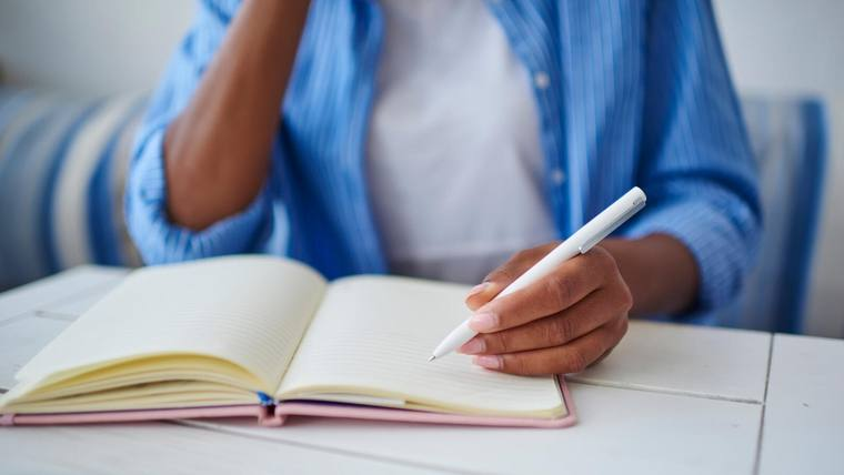 closeup of a woman in a blue shirt sitting at a desk, holding a pen and writing in a book