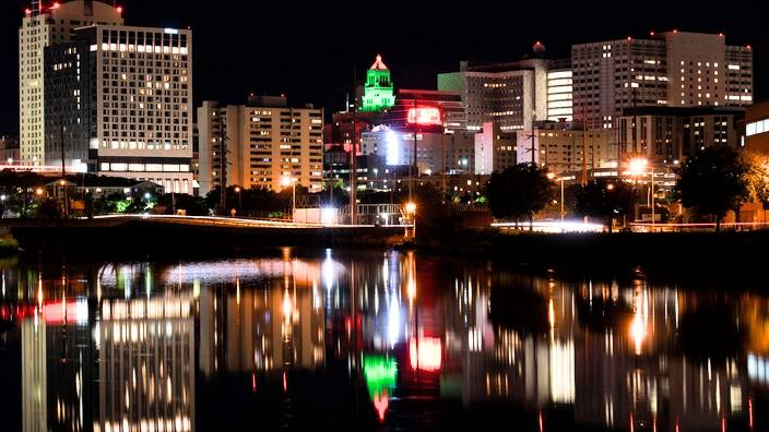 the Rochester MN night skyline with the Plummer Building highlighted in mostly green and red lights in celebration of Juneteenth Day