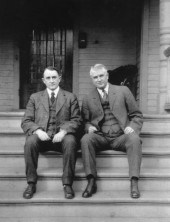 Dr. Charlie Mayo, left, and Dr. Will Mayo sit on the steps of Dr. Will's early home, site of College Apartments today.