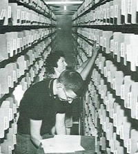 Temporary employee Jay Kvale helps Justine Miller transfer histories from file drawers to the new shelf files.