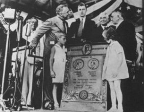 """This photo was taken during President Franklin D. Roosevelt's visit to Rochester. From left to right, are Roosevelt, his son John, Dr. William Mayo and Dr. Charlie Mayo. In front of the president are Waltman Walters, grandson of Dr. Will, and Mildred """"Muff"""" Mayo, granddaughter of Dr. Charlie. (Courtesy of the History Center of Olmsted County.) Photo credit: Post-Bulletin"""