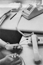 "A plastic transmitter ""reads"" the patient's pulse at the thumbs and relays the message to the Pacemaker Clinic by telephone."