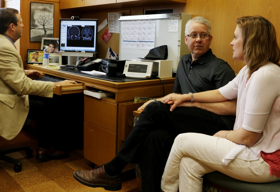 Dr. Jeffrey Britton, a Mayo Clinic neurologist, explains that some minor electrical abnormalities were found in the temporal lobes of Polk County Attorney Greg Widseth, center, who suffered seizures a year ago from an unexplained autoimmune epilepsy disorder. Getting here quickly made a huge difference, Britton told Widseth's wife Nan, a nurse who arranged for her husband to be seen promptly at Mayo. Photo Credit: Dan Browning, Star Tribune