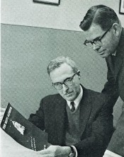"The cover on the first issue of ""The Mayo Alumnus"" was a nighttime view of the illuminated tower on Plummer Building. William J. Holmes, left, was editor of the quarterly publication. At right is Dr. John Higgins, secretary-treasurer of the Alumni Association."