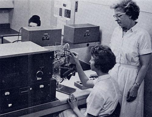 Vera Hanson, supervisor of the routine hematology laboratory, observes as Phyllis Johnson carries out blood counts on the Coulter counter. The sample is taken up by suction in the aperture tube assembly at right and is carried through the counter.