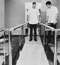 Stan Martin and Bob Mathewson, senior students in the School of Physical Therapy, demonstrate bars which provide support to patients regaining ability to walk.