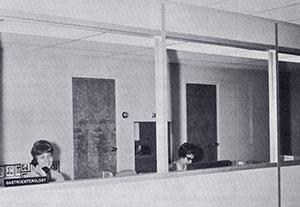 The secretaries' office looks onto the main corridor of the unit, as well as a small waiting area adjacent to the elevators. Secretaries are Mary Olness and Carole Ries.
