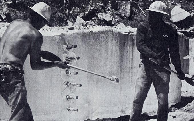 """Wedge holes are drilled into marble with a """"gadder,"""" then workmen drive wedges that force marble to split into blocks of pre-determined size."""