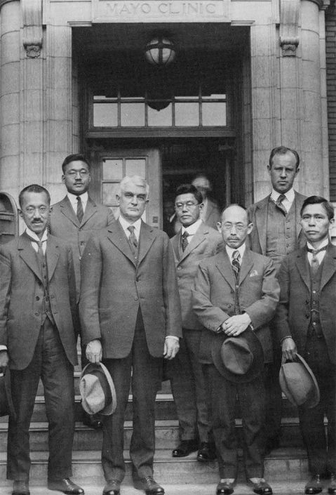 This is how the resurrected entryway stone looked in place in front of the 1914 building, circa 1923. Pictured is Dr. William Mayo (front row) with visiting foreign physicians.