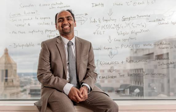 Dr. Athreya sitting on a ledge in front of a window with scientific writing on it, and Rochester, Minnesota, skyline visible through the window.
