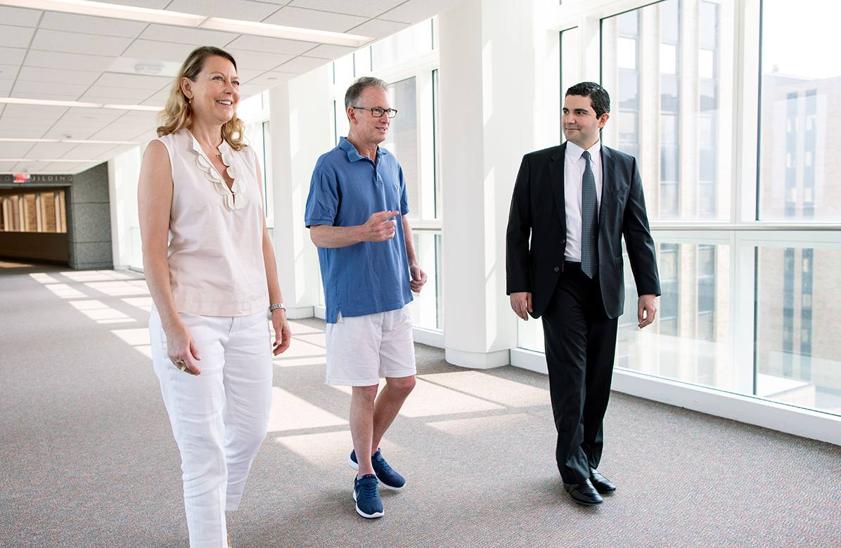Chris Barr, his wife, and his doctor walk together down a hallway