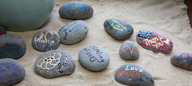 Guests attending the opening of UCLA Operation Mend's new intensive mental health program wite messages of hope on rocks as inspiration for future patients. Photo credit: Reed Hutchinson/UCLA