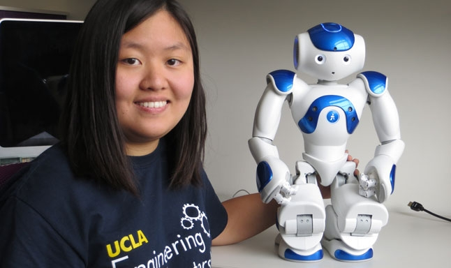 Sunnie So, an undergraduate researcher with UCLA Engineering, poses with a robot that can serve as a medical companion for elderly people recovering from injury or illness.