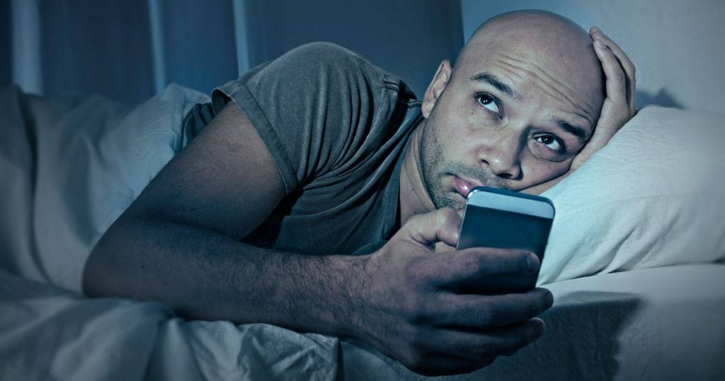 Man laying in bed looking at mobile phone with a distressed face