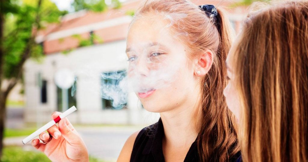 Young teenager using e-cigarette
