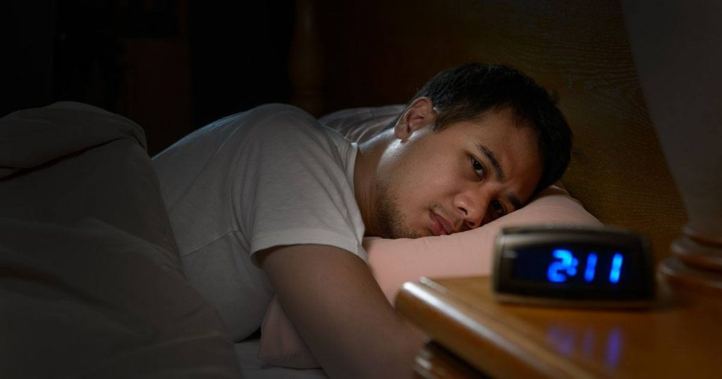 Man laying in bed looking at alarm clock