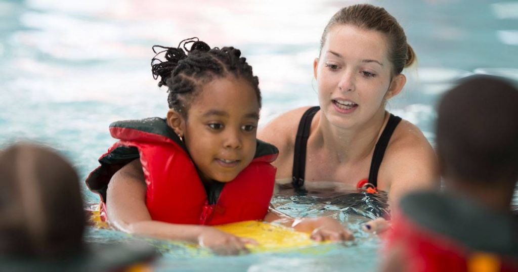 Child swimming in a pool with instructor