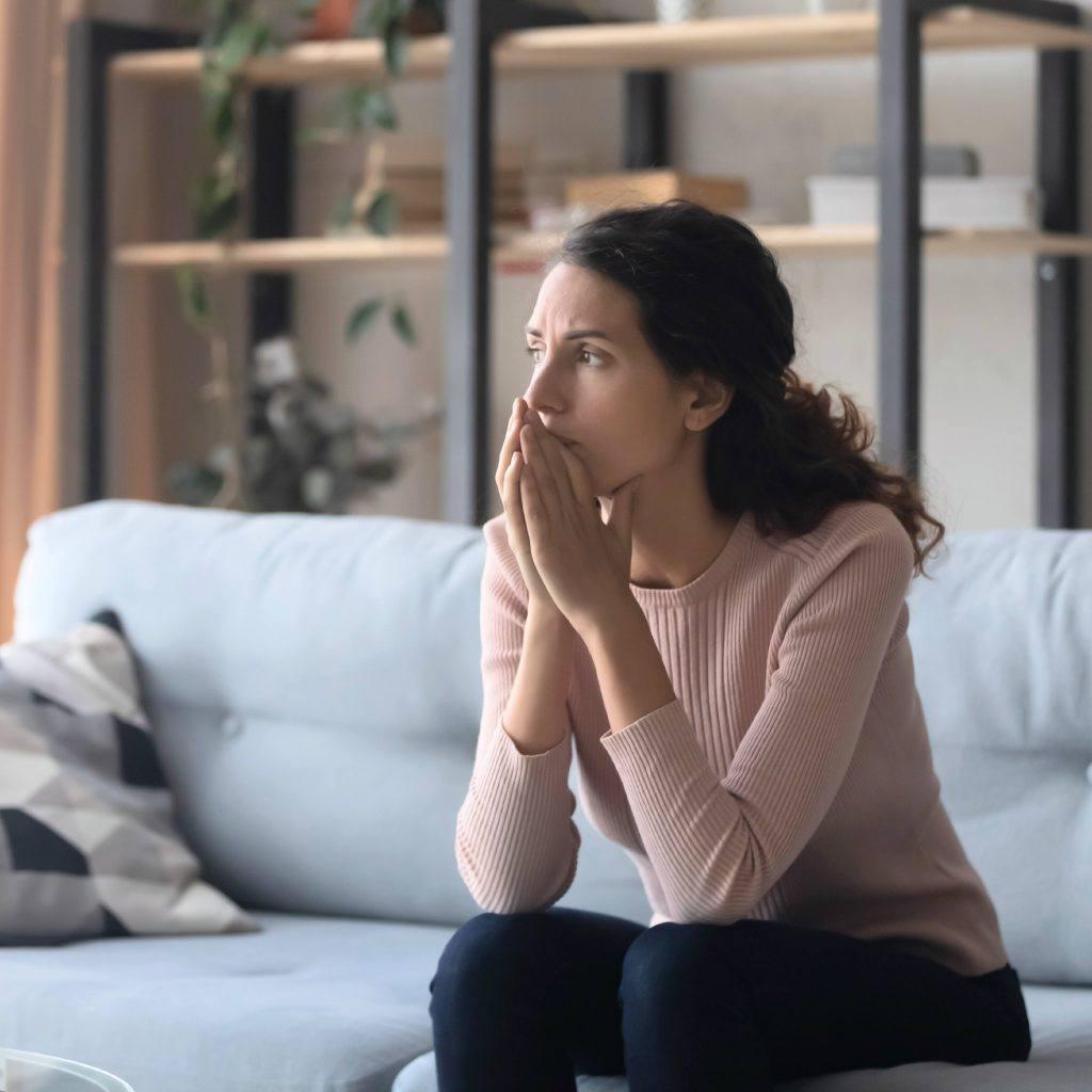 uma mulher sentada em um sofá olhando pela janela, cruzando as mãos e parecendo triste, preocupada, preocupada