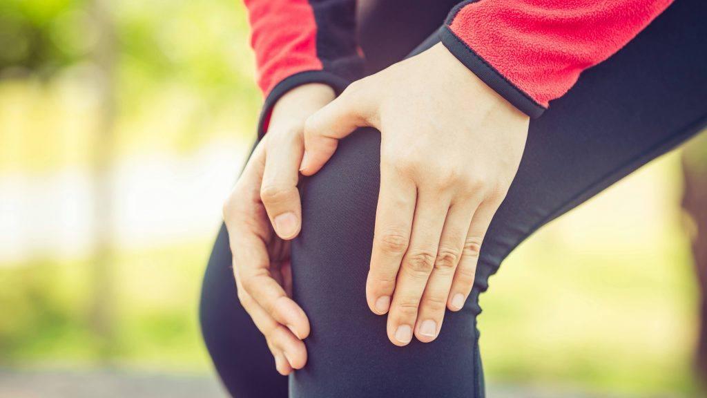 uma mulher com macacão de corrida segurando a área da perna e do joelho como se sentisse dor após uma lesão