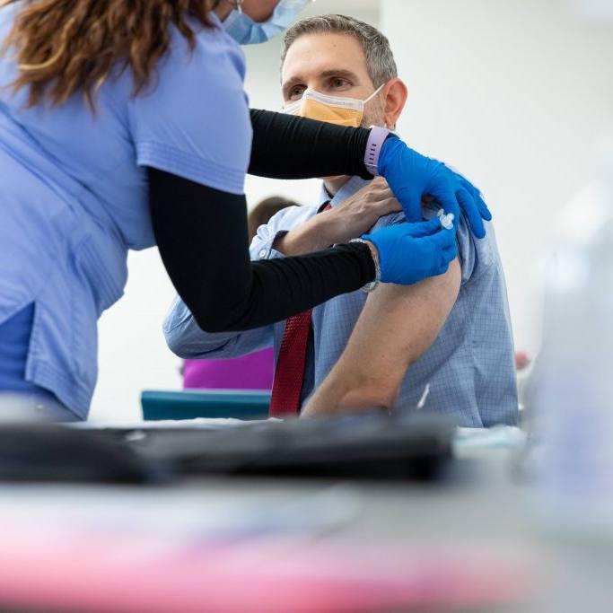 homem de meia-idade sendo vacinado para COVID-19 por profissional de saúde