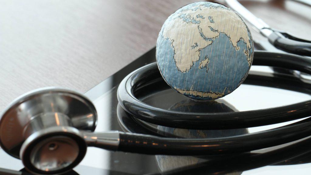Um estetoscópio com um pequeno globo sobre a mesa para representar a saúde mundial