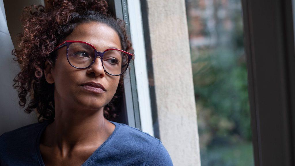 retrato de uma mulher de meia-idade perto de uma janela, parecendo triste, deprimida, solitária