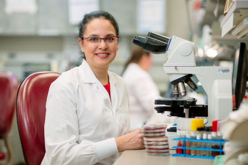 Dr. Robin Patel sitting in front of a microscope surrounded by vials and petri dishes in her Rochester, Minnesota lab.