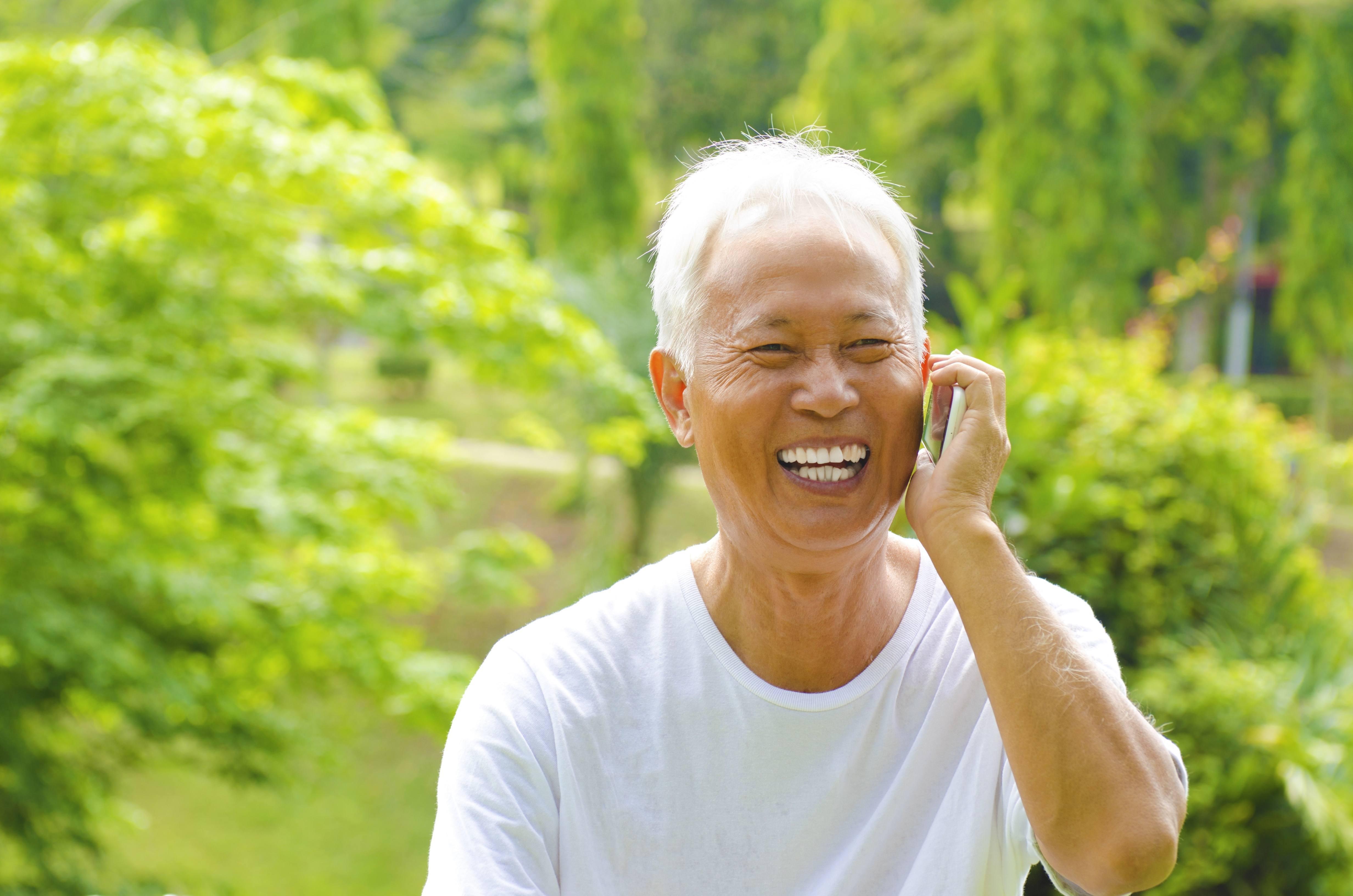 电话室外绿色公园的健康资深亚裔人