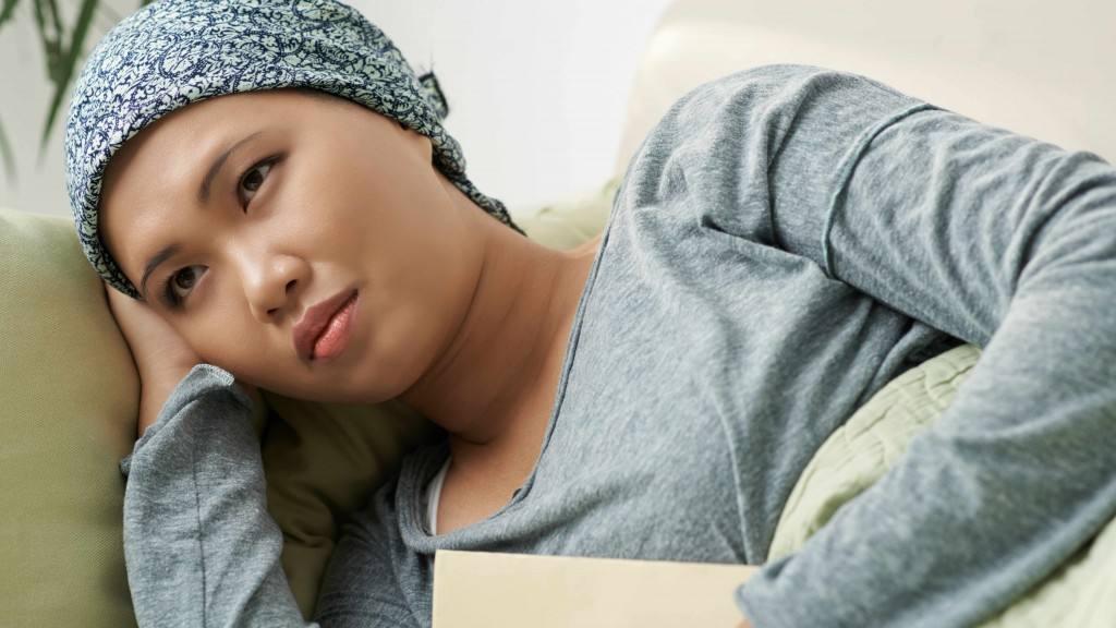 一个悲伤的女人,她的头上戴着头巾,也许是化疗后的癌症患者