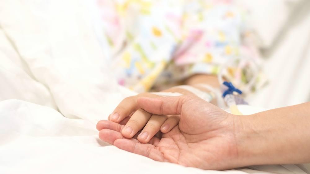 一名静脉输液的儿童患者在医院的床上手牵着手睡觉,一名成人握着她的手为安慰