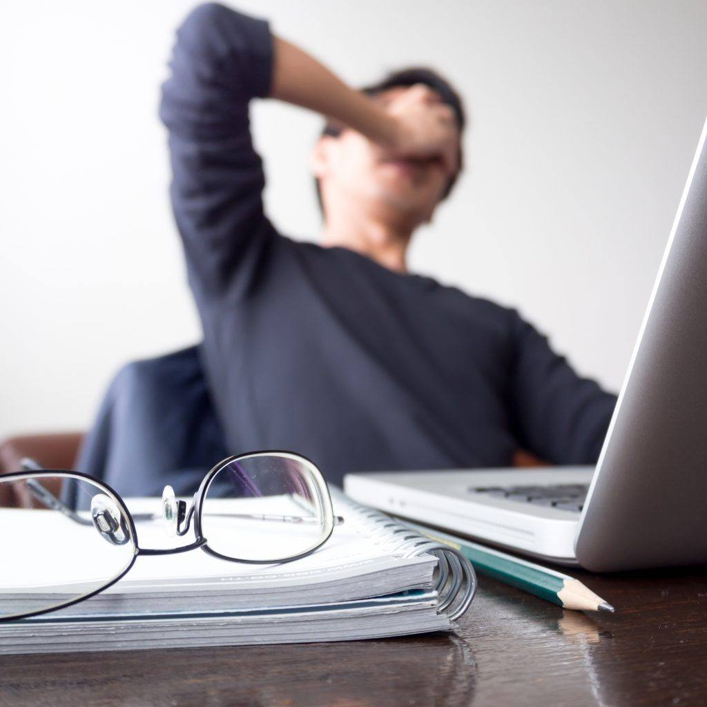 手握着脸的男子,在木桌上用笔记本电脑和带眼镜的笔记本电脑工作,休息了一段时间