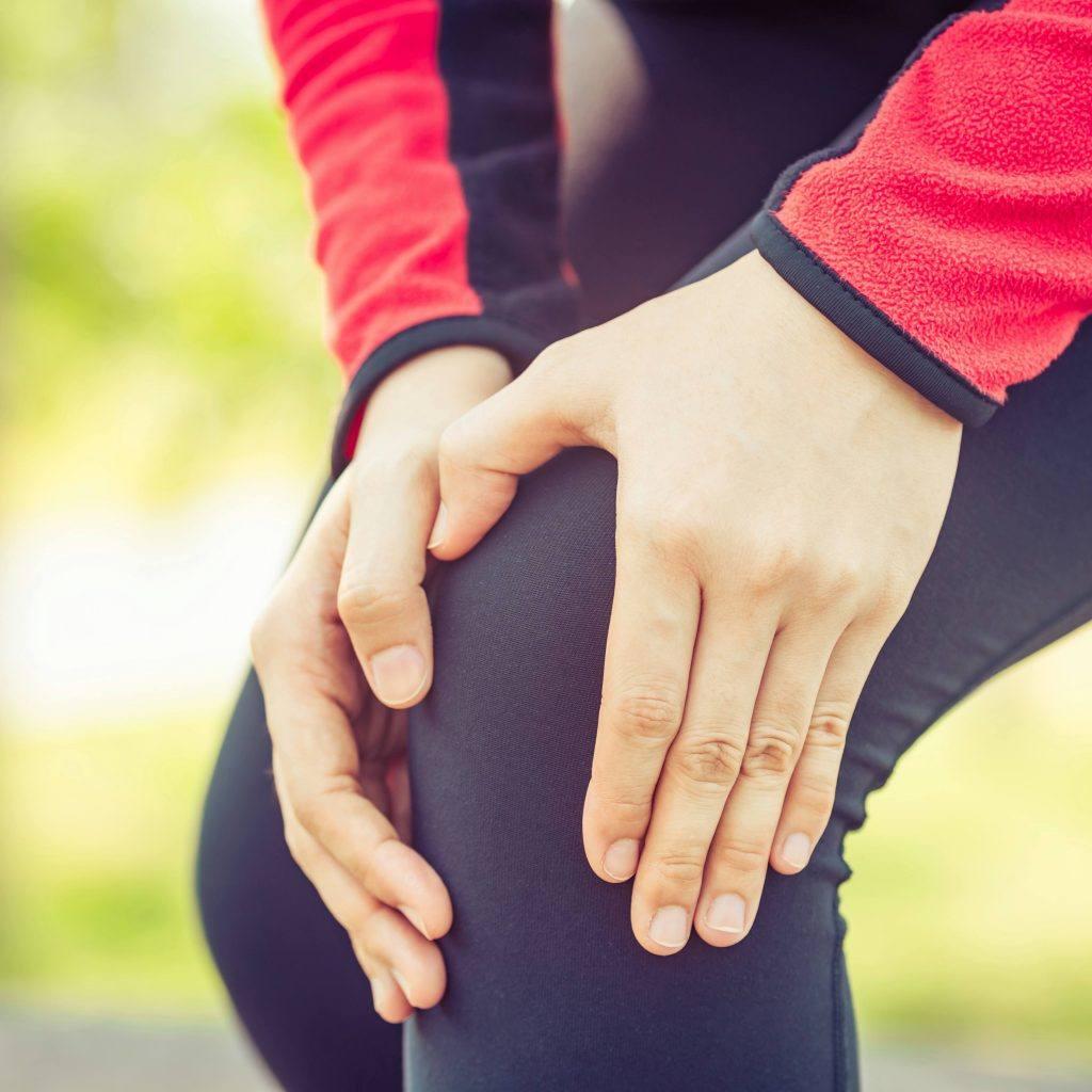 一个穿着运动慢跑服的女人抱着她的腿和膝盖区域,好像受伤后感到疼痛