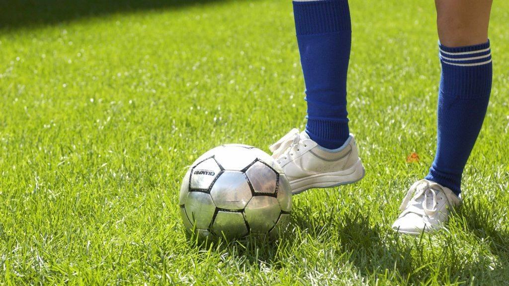 脚和腿靠近足球; 脚踢足球