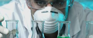 Scienist peering closely at beakers, wearing gown, mask, gloves, goggles.