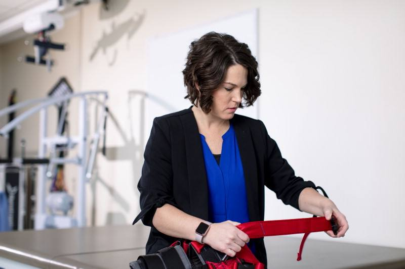 Megan Gill, seated, adjusts red harness straps.
