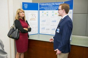 Tim Kellet, wearing slacks and a blue sport coat, stands in front of his research poster. A woman,  wearing a red dress and black cardigan, listens to him speak.