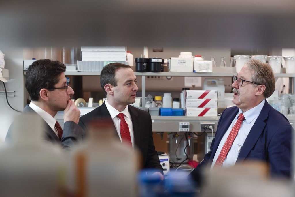 three male researchers in suits in lab, Dr. Gores on right