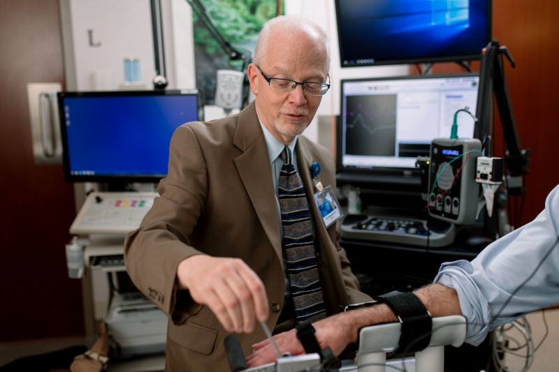 Brian Weinshenker, M.,D., works with a multiple sclerosis patient to measure finger extensor weakness.