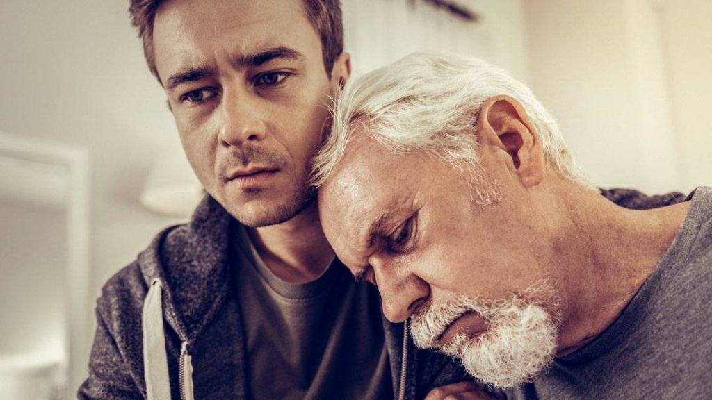 Man sits with his elderly father's head on his shoulder