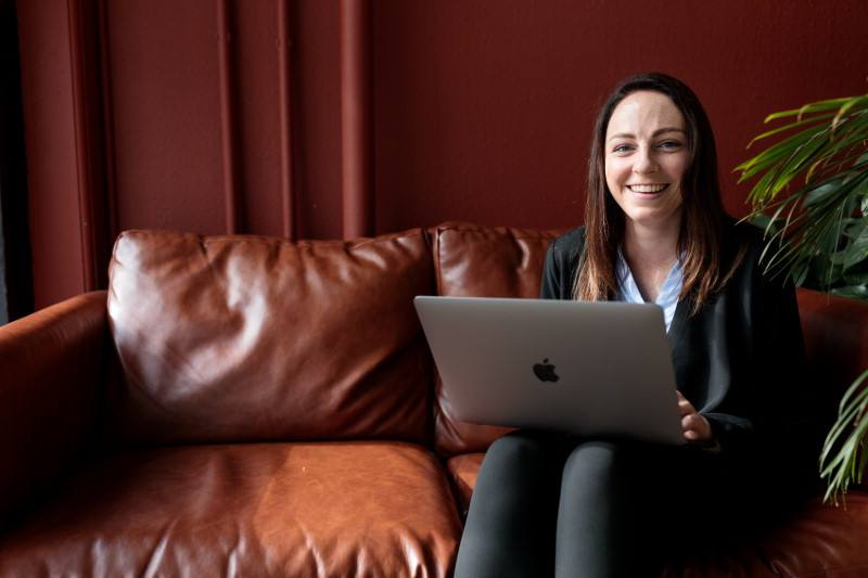 Emma Goddery site on a leather couch working on a laptop, smiling into the camera