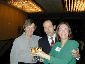 Drs. Rizza, Vella and Conover pose  at a holiday party. Dr. Conover precariously holds three full beverages.