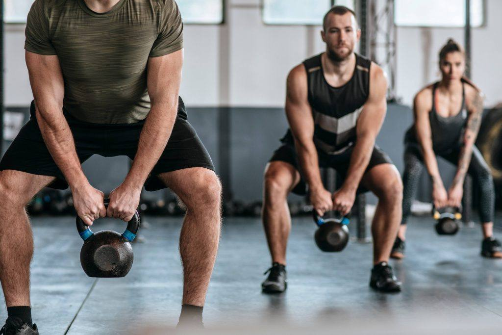 group of people lifting kettlebells in a fitness class