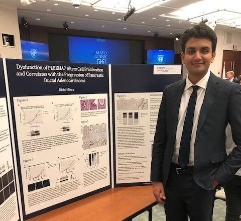 Rishi Misra standing next to his three-paneled poster displayed on a table in poster exhibit hall