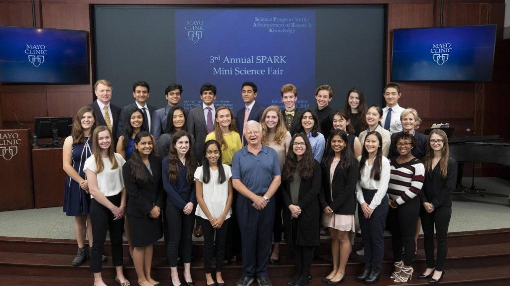 diverse group of high school students posing with Mayo researchers on a raised stage with SPARK signage on screens behind