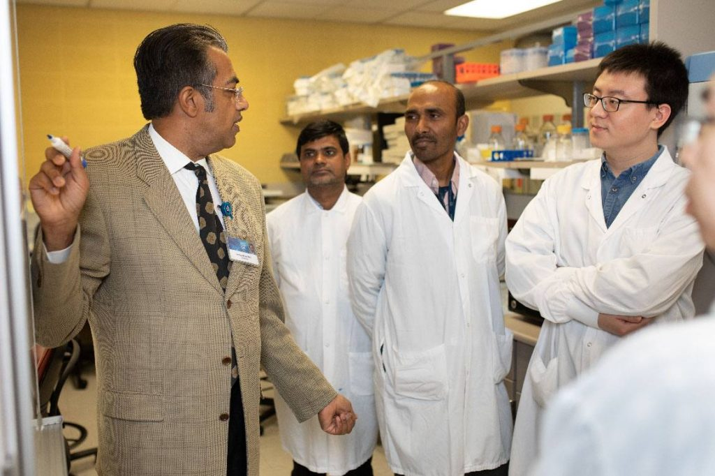 Dr. Misra on left, explaining something to several members of his lab team, using white board and marker.